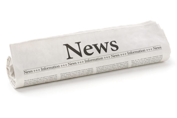 A rolled newspaper with the headline News