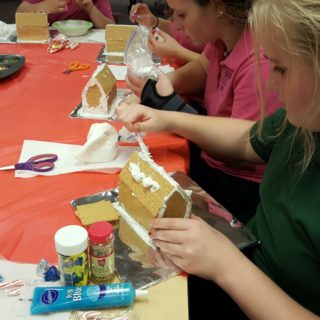 Gingerbread houses are being built by several St. Justin Martyr students today. Devouring some of the decorations was part of the fun!