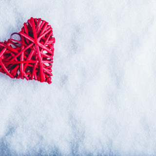 Beautiful romantic vintage red heart on a white snow winter background. Love and St. Valentines Day concept.
