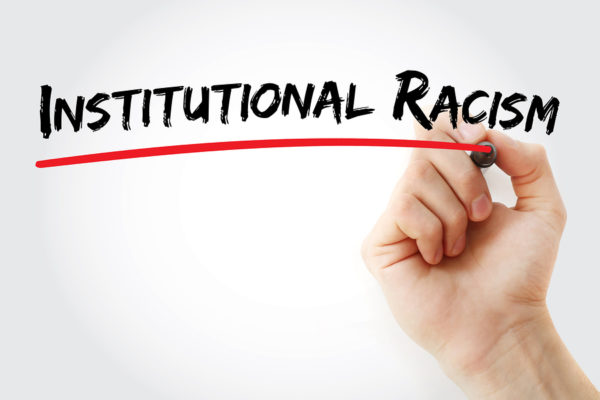 Hand writing Institutional racism with marker concept background